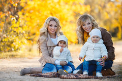 Moms and kids for a walk in the park in autumn Stock Images