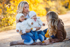 Moms and kids for a walk in the park in autumn Stock Photos