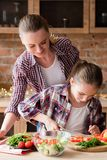 Helper girl salad dinner family cooking leisure. Moms little helper. kid girl preparing salad for dinner. mom watching. happy family cooking leisure and good royalty free stock photos