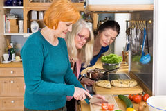 Moms Looking at their Friend Slicing Ingredients Stock Photography