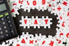 Moms momsbegrepp, vit pusselfigursåg med alfabetet som bygger ordet moms med räknemaskinen på mitten av mörker royaltyfri foto