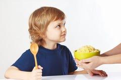 Momtakes pläterar av porridge till henne lite barnet Royaltyfri Bild