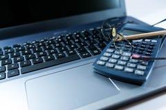 Monóculo, lápis, calculadora no teclado de laptop, imagem de fundo do negócio, fotografia de stock
