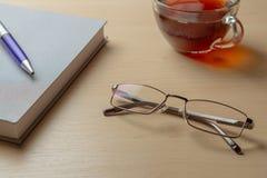 Monóculos, diário, pena azul e copo do chá em uma tabela marrom, foco seletivo fotografia de stock