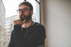 Monóculos vestindo da forma do homem considerável novo contra janelas panorâmicos no fundo borrado com lotes do espaço da cópia Imagem de Stock