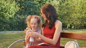 Monóculos vestindo da mãe nova que leem com sua filha pequena que senta-se no banco no parque Menina com dois vídeos de arquivo