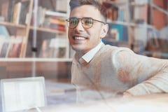 Monóculos vestindo do homem alegre ao sentar-se no café Imagens de Stock Royalty Free