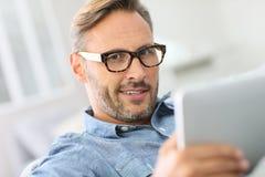 Monóculos vestindo do homem considerável e websurfing fotografia de stock