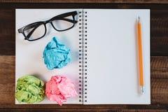 Mon?culos, papel amarrotado e caderno espiral vazio com espa?o da c?pia em uma tabela de madeira imagens de stock royalty free