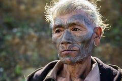 Mon Headhunter. Longwa, Nagaland/India - December 8, 2013: Elderly Tattooed faced former Mon Headhunter from Longwa Village. Naga tribes practised headhunting royalty free stock photography