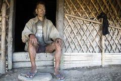 Mon Headhunter. Longwa, Nagaland/India - December 8, 2013: Elderly Tattooed faced former Mon Headhunter from Longwa Village. Naga tribes practised headhunting royalty free stock image
