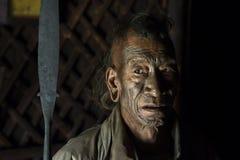 Mon Headhunter. Longwa, Nagaland/India - December 8, 2013: Elderly Tattooed faced former Mon Headhunter from Longwa Village. Naga tribes practised headhunting stock photos