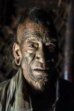 Mon Headhunter. Longwa, Nagaland/India - December 8, 2013: Elderly Tattooed faced former Mon Headhunter from Longwa Village. Naga tribes practised headhunting royalty free stock photo