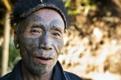 Mon Headhunter. Longwa, Nagaland/India - December 8, 2013: Elderly Tattooed faced former Mon Headhunter from Longwa Village. Naga tribes practised headhunting stock image