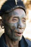 Mon Headhunter. Longwa, Nagaland/India - December 8, 2013: Elderly Tattooed faced former Mon Headhunter from Longwa Village. Naga tribes practised headhunting stock photography