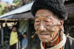 Mon Headhunter. Longwa, Nagaland/India - December 9, 2013: Tattooed face of elderly former Mon Headhunter from Longwa Village. Naga tribes practised headhunting stock image