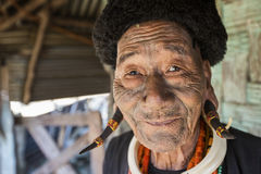 Mon Headhunter. Longwa, Nagaland/India - December 9, 2013: Tattooed face of elderly former Mon Headhunter from Longwa Village. Naga tribes practised headhunting stock photos
