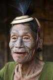 Mon Headhunter. Singha Chingnyu, Nagaland/India - December 8, 2013: Elderly Tattooed faced former Mon Headhunter from Singha Chingnyu. Naga tribes practised royalty free stock image