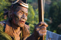 Mon Headhunter. Singha Chingnyu, Nagaland/India - December 8, 2013: Elderly Tattooed faced former Mon Headhunter from Singha Chingnyu. Naga tribes practised stock photography