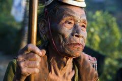 Mon Headhunter. Singha Chingnyu, Nagaland/India - December 8, 2013: Elderly Tattooed faced former Mon Headhunter from Singha Chingnyu. Naga tribes practised stock photos