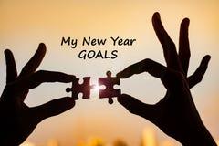 Mon mot de buts de nouvelle année avec des mains reliant le morceau de puzzle de couples contre l'effet de lever de soleil, puzzl photo libre de droits