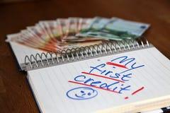 Mon premier crédit écrit sur un bloc-notes avec quelques factures d'euro hors focale à l'arrière-plan Photos libres de droits