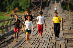 Mon refugee kids cross saphan mon wooden bridge. Chidren from the mon village aka wangka crossing saphan mon, or mon bridge. 400 m. long, made by hand, wooden Stock Photos