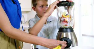 Mon and son preparing juice. With blender in a kitchen stock footage