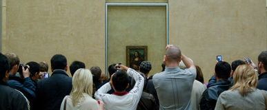 Mona Lisa crowd. Group of tourists gathered around the Mona Lisa in the Louvre Museum, taking pictures Stock Photo