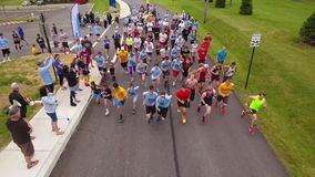 High angle view of Charlottes run starting line. Monaca, PA - Circa May, 2017 - A high angle aerial view of runners at the starting line of Charlotte's Run 28, a stock video