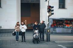 Monachium, Niemcy, Grudzień 29, 2016: Ludzie stoją przy światłami ruchu i przygotowywają krzyżować drogę Codzienna rutyna Zdjęcia Stock