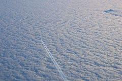 MONACHIUM NIEMCY, JAN, - 21st, 2017: samolot lata w białych chmurach w niebieskim niebie i opuszczać ślad, jak widzieć od inny Zdjęcie Stock