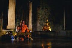 Monaco anziano asiatico che pensa per la scrittura del qualcosa al sanct di Ayutthaya Fotografie Stock