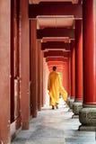 Monaco buddista che cammina lungo il corridoio di legno rosso di un monastero immagini stock libere da diritti
