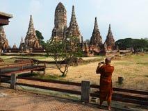 Monaco buddista che prende un'immagine del tempio con uno smartphone immagine stock
