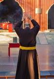 Monaco che prega con le mani sollevate in un'iarda del tempio buddista a Pechino, Cina Visto da dietro immagine stock libera da diritti