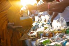Monaco che ricevono alimento e oggetti che offrono dalla gente Immagini Stock