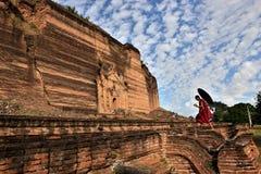 Monaco con l'ombrello rosso che cammina in un tempio buddista fotografia stock