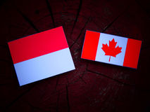 Monaco flag with Canadian flag on a tree stump isolated Stock Photo