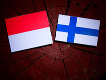 Monaco flag with Finnish flag on a tree stump isolated Royalty Free Stock Photos