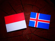 Monaco flag with Icelandic flag on a tree stump isolated Royalty Free Stock Photo