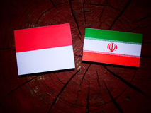 Monaco flag with Iranian flag on a tree stump isolated. Monaco flag with Iranian flag on a tree stump Stock Images