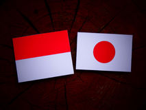 Monaco flag with Japanese flag on a tree stump isolated Royalty Free Stock Images