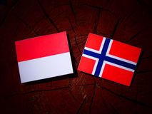 Monaco flag with Norwegian flag on a tree stump isolated Stock Photo