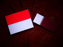 Monaco flag with Qatari flag on a tree stump isolated. Monaco flag with Qatari flag on a tree stump Royalty Free Stock Photography