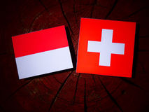 Monaco flag with Swiss flag on a tree stump  Royalty Free Stock Photography