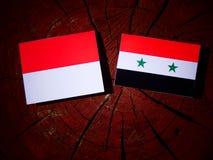 Monaco flag with Syrian flag on a tree stump isolated. Monaco flag with Syrian flag on a tree stump Royalty Free Stock Image