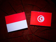 Monaco flag with Tunisian flag on a tree stump isolated Royalty Free Stock Image