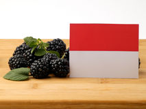Monaco flag on a wooden panel with blackberries isolated on a wh Royalty Free Stock Images
