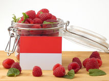 Monaco flag on a wooden panel with raspberries isolated on a whi Stock Photos
